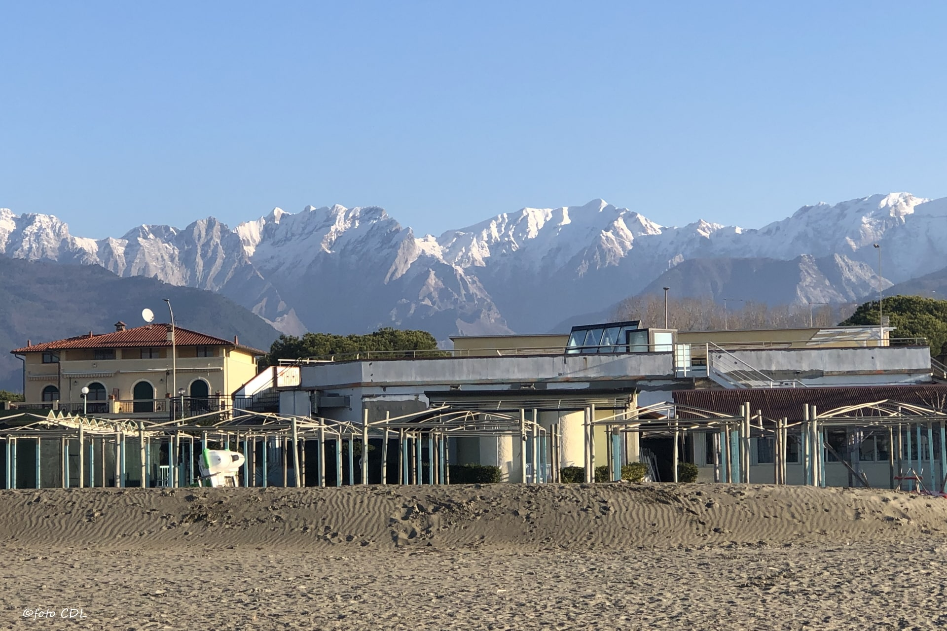 Marina di Massa: stabilimenti balneari e le Alpi Apuane innevate